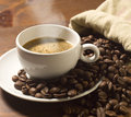 Coffee cup and grains on wooden table Royalty Free Stock Image