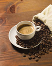 Coffee cup and grains on wooden table Royalty Free Stock Photography