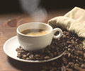 Coffee cup and grains on wooden table Royalty Free Stock Photos