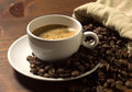 Coffee cup and grains on wooden table Stock Photography