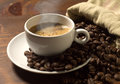 Coffee cup and grains on wooden table Royalty Free Stock Photo
