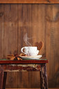 Coffee cup and heart cookie cinnamon sticks sugar anise star on wooden table stool on brown wood background Royalty Free Stock Photos