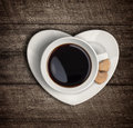 Coffee cup and heart shape saucer valentine concept top view on wooden table Royalty Free Stock Photo