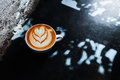 Coffee cup with latte art on the floor Royalty Free Stock Photo