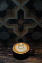 Coffee cup with latte art in front of abstract wall Royalty Free Stock Photo