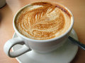 Coffee in a cup of latte with leaf pattern the froth Royalty Free Stock Photography