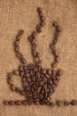 Coffee cup made ​​of coffee beans on a burlap Royalty Free Stock Photo
