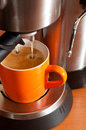 Coffee cup in the percolator orange from hot esppresso Royalty Free Stock Photo