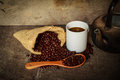 Coffee cup sack scoop of coffee beans and kettle on the old wood Royalty Free Stock Photo