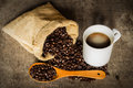 Coffee cup sack scoop of coffee beans on the old wooden floor. Royalty Free Stock Photo