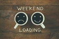 Coffee cup with sad and happy faces next to weekend loading phrase background. vintage filtered. happy weekend concept
