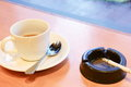 Coffee cup and spoon with black ashtray cigarette Royalty Free Stock Photo