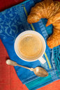 Coffee cup with spoon and croissant on blue kitchen towel top view Royalty Free Stock Image