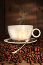 Coffee cup with spoon on roasted beans Royalty Free Stock Photo