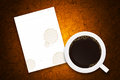 Coffee cup and white paper on brown grunge concrete Stock Image