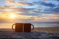 Coffee cup on wood log at sunset or sunrise beach Royalty Free Stock Photo