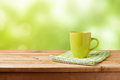 Coffee cup on wooden table over green bokeh background. Mock up for logo design display Royalty Free Stock Photo