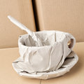 Coffee cup wrapped in paper a large and a spoon light brown standing among moving carton boxes Royalty Free Stock Image