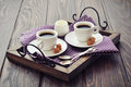 Coffee in cups with spoon and milk on vintage wooden tray Stock Photo