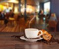 Coffee drink in cafeteria served with croissant on wooden table with blur as background Stock Photo