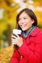 Coffee drinking woman in autumn fall enjoying fall and hot drink from disposable cup smiling happy asian female model Royalty Free Stock Image