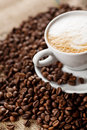 Coffee foam a pile of beans with cup of in saucer Royalty Free Stock Image