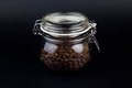 Coffee grains in glass jar on a black background Royalty Free Stock Photo