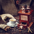 Coffee grinder hot cup of and fresh beans and Stock Photos