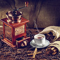 Coffee grinder hot cup of and fresh beans and Stock Images