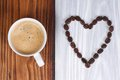 Coffee and heart from coffee beans on a wooden surface Stock Photography