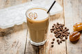 Coffee ice cubes and beans with latte on wooden desk background Royalty Free Stock Photo