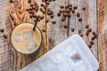 Coffee ice cubes and beans with latte on wooden desk background top view Royalty Free Stock Photo