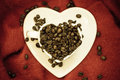 Coffee klatsch java concept. Heart shaped cup filled with roasted coffee beans Royalty Free Stock Photo