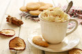 Coffee a la vienne and crumbly cookies on wooden table cup of whipped cream powdered with cinnamon pile of apple background Stock Photo