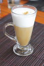 Coffee latte with frothy milk in tall glass cup of on table cappuccino Royalty Free Stock Image