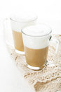 Coffee latte in glass mugs on white table Royalty Free Stock Images