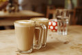 Coffee latte in two tall glasses and sugar bowl shallow dof Royalty Free Stock Images