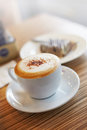 Coffee in light close up coffe cup with capuchino and cake street cafe Royalty Free Stock Images
