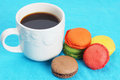 Coffee and macarons on blue cup of black colorful Stock Image