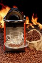 Coffee machine with cup of espresso near fireplace and a empty glass stand a bag beans against the bright flame Royalty Free Stock Photography