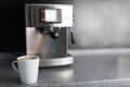 Coffee machine and freshly made cup of latte of table Stock Images