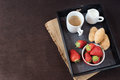 Coffee, mini French pastries and strawberries on wooden tray over black table. Black background Royalty Free Stock Photo