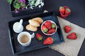 Coffee, mini French pastries and strawberries on wooden tray over black table. White and purple flowers in a decorative wooden cra Royalty Free Stock Photo