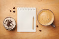 Coffee mug with cupcake, notebook and pencil on rustic table from above, good morning or have a nice day concept Royalty Free Stock Photo