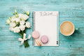 Coffee mug with macaron, white flowers and notebook with to do list on blue rustic table from above. Beautiful breakfast. Flat lay Royalty Free Stock Photo