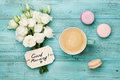 Coffee mug with macaron, white flowers and notes good morning on blue rustic table from above. Beautiful breakfast. Flat lay. Royalty Free Stock Photo