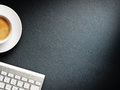 Coffee mug on the table with a keyboard close up Royalty Free Stock Photos