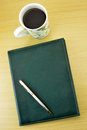 Coffee notebook and pen on wooden table Stock Images