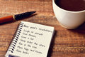 Coffee and notepad with a list of new years resolutions Royalty Free Stock Photo