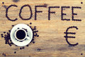 Coffee offer beans cup and euro symbol on wooden table Stock Photos
